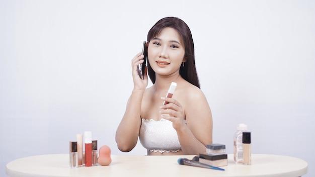 Schöne asiatische make-up-diskussion am telefon isoliert auf weißem hintergrund
