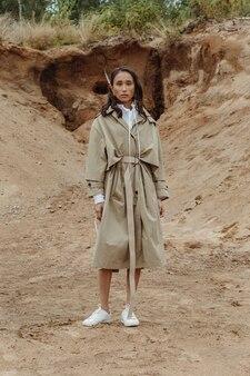 Schöne asiatische modefan in einem trenchcoat, der vor sandgrube aufwirft. vertikales bild.