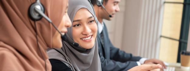 Schöne asiatische moslemische frau, die im kundenkontaktcenter mit team, panoramische fahne arbeitet
