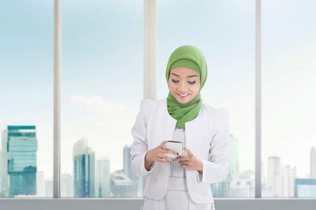 Schöne asiatische moslemische frau mit handy