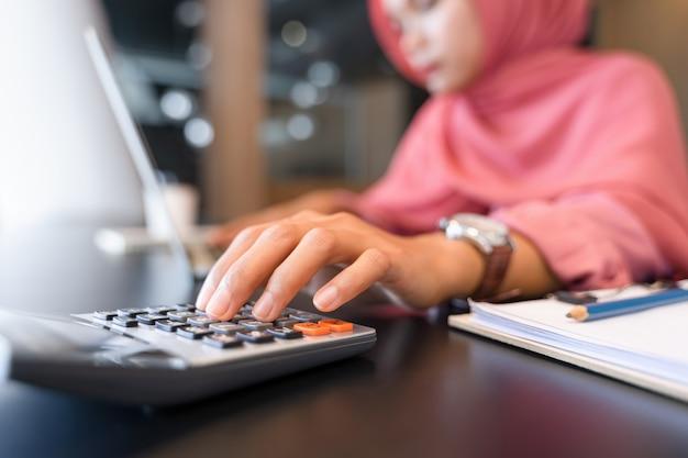 Schöne asiatische moslemische geschäftsfrau im rosa hijab und in der freizeitkleidung, die mit taschenrechner arbeitet