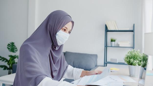 Schöne asiatische muslimische dame trägt gesichtsmaske mit laptop und geschäftsberichten im wohnzimmer.