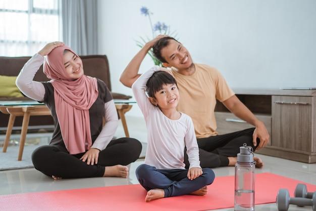 Schöne asiatische muslimische familie, die zu hause zusammen trainiert. eltern und kind machen sport, der sich im wohnzimmer ausdehnt