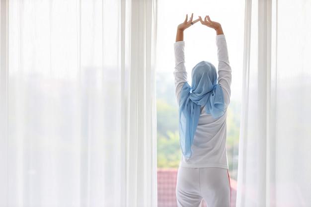 Schöne asiatische muslimische frau der rückansicht, die weiße nachtwäsche trägt und ihre arme streckt, nachdem sie am morgen bei sonnenaufgang aufgestanden ist. nette junge frau mit blauem hijab, der steht und sich beim wegschauen entspannt