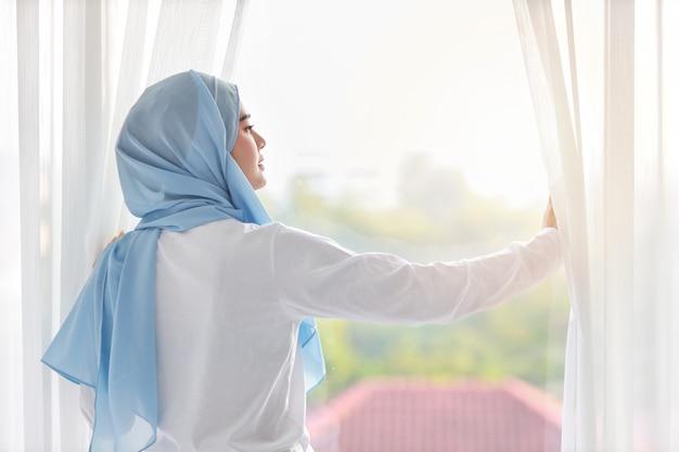Schöne asiatische muslimische frau der rückansicht, die weiße nachtwäsche trägt und ihre arme streckt, nachdem sie am morgen bei sonnenaufgang aufgestanden ist. nettes junges mädchen mit blauem hijab stehend und entspannend beim wegsehen