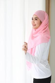 Schöne asiatische muslimische frau der seitenansicht, die weiße nachtwäsche trägt
