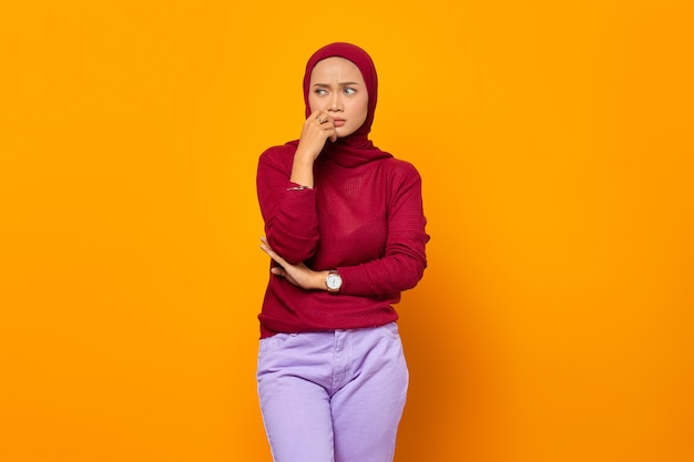Schöne asiatische muslimische frau, die an etwas denkt und ihr kinn berührt