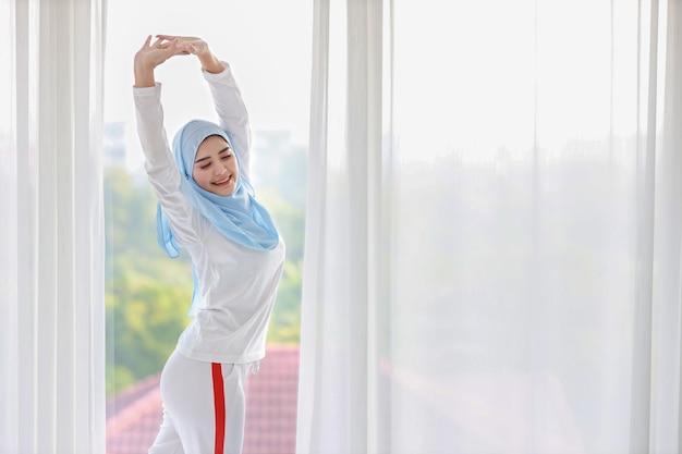 Schöne asiatische muslimische frau, die weiße nachtwäsche trägt und ihre arme streckt, nachdem sie am morgen bei sonnenaufgang aufgestanden ist. nette junge frau mit blauem hijab stehend und entspannend mit glücklichem und lächelndem gesicht.