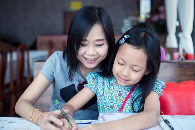 Schöne asiatische mutter, die ihrer tochter bei den hausaufgaben hilft