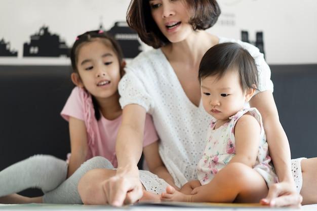 Schöne asiatische mutter, die ziemlich geschichtengeschichtenbuch mit ihren kindern auf dem bett liest.