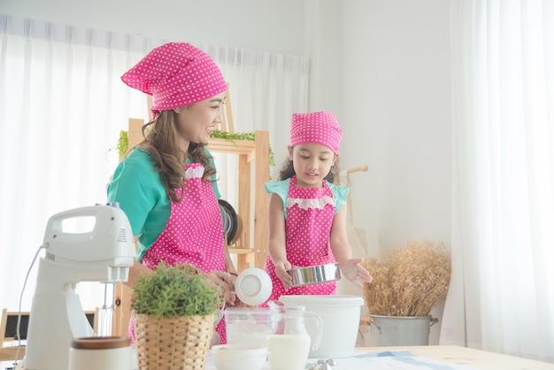 Schöne asiatische mutter und tochter, die das rosa schutzblech macht kuchen in der küche trägt.