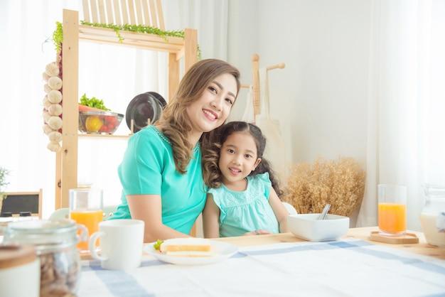 Schöne asiatische mutter und tochter, die morgens zusammen zu hause frühstückt