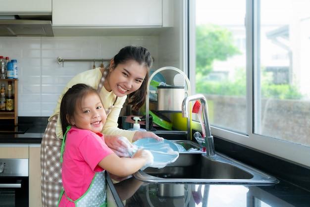 Schöne asiatische mutter und tochter, die spaß beim geschirr spülen zusammen mit reinigungsmittel auf wanne in der küche zu hause hat. glückliche familienzeit zu unterrichtender tochter zur hausarbeit.