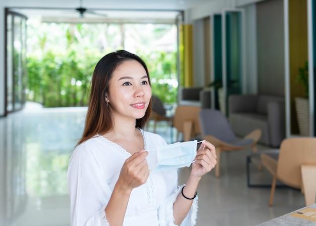 Schöne asiatische reisende frau, die schützende gesichtsmaske auf ihren händen hält neues normales gesundheitsreise- und urlaubskonzept