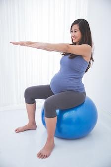 Schöne asiatische schwangere frau, die übung mit einem schweizer ball tut