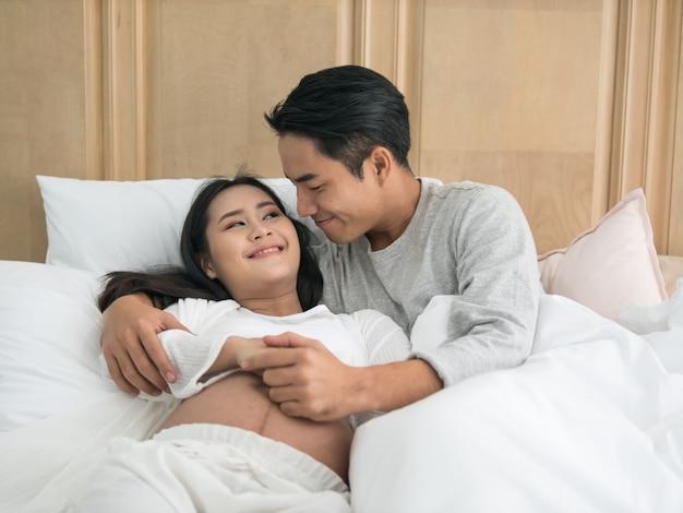Schöne asiatische schwangere frau und ihr hübscher ehemann, die auf das bett beim zeit zusammen verbringen legt.