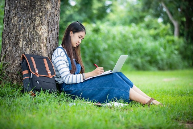Schöne asiatische studentin, die bücher und lächeln und lern- und bildungskonzept auf park im sommer für entspannungszeit hält