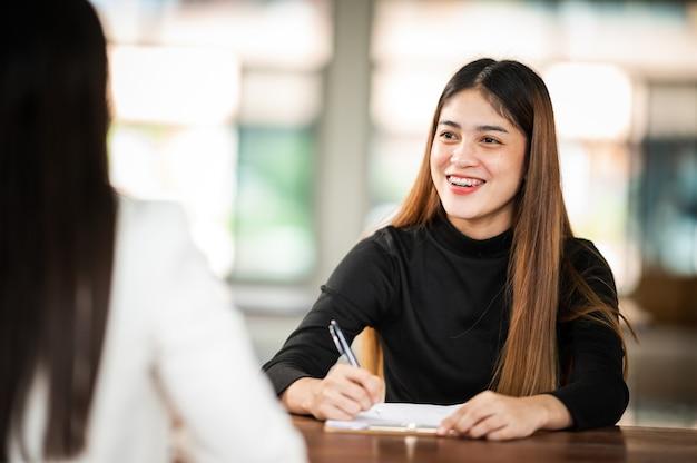 Schöne asiatische studentin sitzt zur prüfung an der universitätsklasse studenten, die in der reihe bildung lifestyle university college sitzen