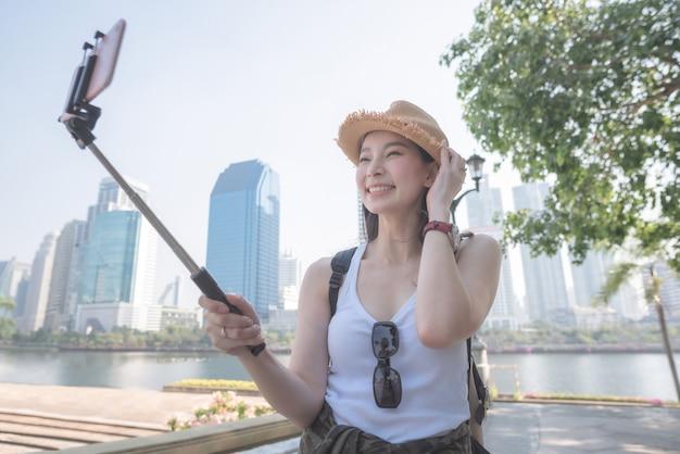 Schöne asiatische touristische frau, die selfies auf einem smartphone in der städtischen stadt im stadtzentrum gelegen nimmt.