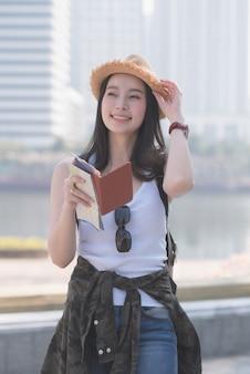 Schöne asiatische touristische solofrau, die nach besichtigungsstelle der touristen lächelt und sucht.