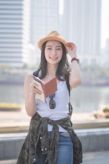 Schöne asiatische touristische solofrau, die nach besichtigungsstelle lächelt und sucht.