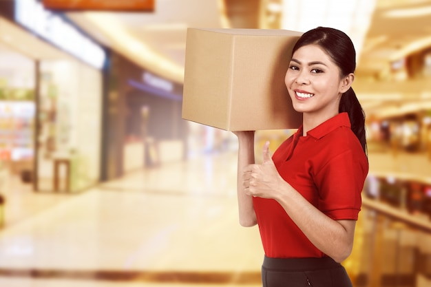 Schöne asiatische weibliche lieferung, die das paket hält