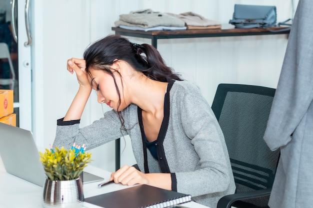 Schöne asiatische zufällige frau ermüdete während des arbeitsstart-kleinunternehmers sme im kleidungsshop.