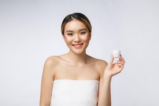 Schöne asien-frau, die das produkt lokalisiert auf weißem hintergrund darstellt.