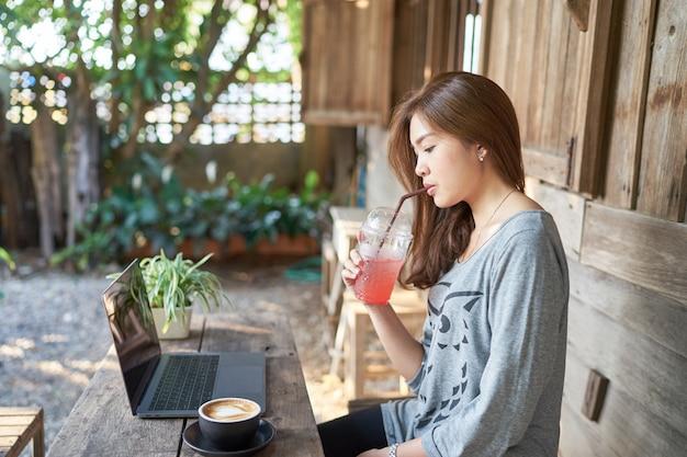 Schöne asien-frau, die italienisches soda trinkt und laptop an der weinlesekaffeestube verwendet