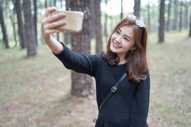 Schöne asien-frau mit dem braunen haar, das selfie im kiefernpark nimmt