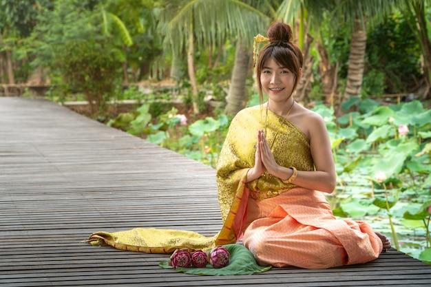 Schöne asien-frauen, die traditionelles thailändisches kleid tragen und auf holzbrücke sitzen.