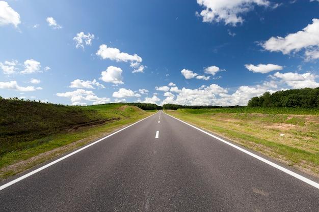 Schöne asphaltstraße mit blauem himmel und mischwald am horizont, sommerlandschaft mit bewölktem himmel