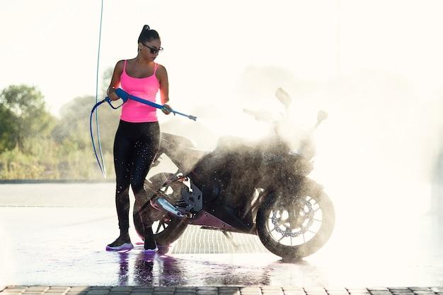 Schöne atemberaubende frau wäscht ein motorrad in selbstbedienungs-autowaschanlage mit hochdruckwasserstrahl am morgen bei sonnenaufgang.