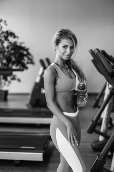 Schöne athletische blonde frau trinkt wasser auf einem laufband in der turnhalle