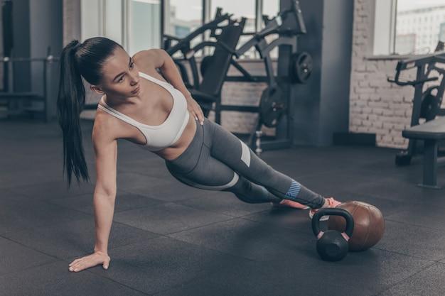 Schöne athletische frau, die an der turnhalle, seitenplanke tuend, kopienraum trainiert