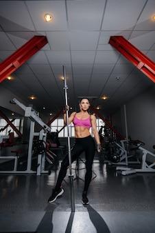 Schöne, athletische frau, die im fitnessstudio nach einem harten training aufwirft. fitness, bodybuilding.