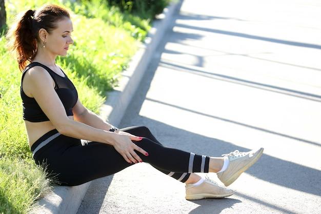 Schöne athletische frau, die knie nach verletzung festhält