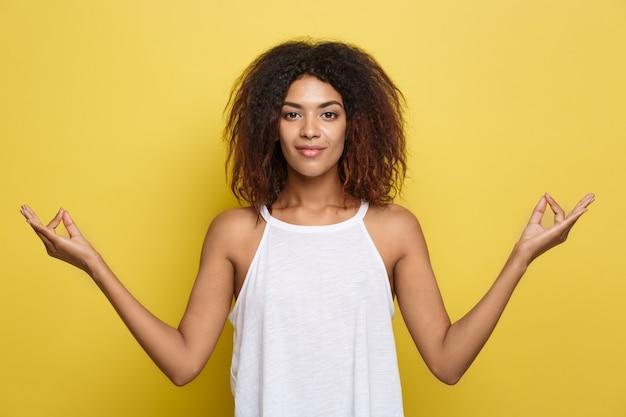 Schöne attraktive african american frau mit trendy brille posting über gelb studio hintergrund. text kopieren