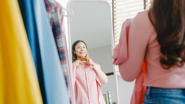 Schöne attraktive dame, die kleidung auf kleiderständer auswählt und sich im spiegel im schlafzimmer im haus anzieht