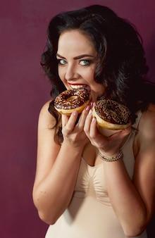 Schöne attraktive dunkelhaarige frau mit bunten leckeren glasierten donuts
