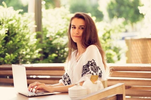 Schöne attraktive frau am café mit einem laptop, der eine kaffeepause hat