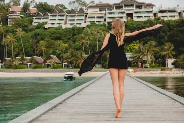 Schöne attraktive frau gekleidet im schwarzen kleid, das auf pier im luxusresorthotel, sommerferien, tropischer strand aufwirft