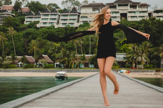 Schöne attraktive frau gekleidet in romantisches schwarzes kleid, das auf pier im luxusresorthotel aufwirft,
