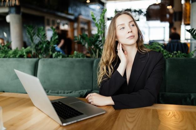 Schöne attraktive frau im café mit einem laptop, der eine kaffeepause hat