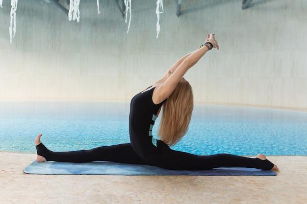 Schöne attraktive frauenpraxis-yogahaltung auf dem pool morgens, entspannen sich im feiertag oder im freien tag.