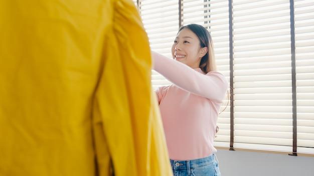 Schöne attraktive junge asia-dame, die ihre mode-outfit-kleidung im schrank im haus oder im laden auswählt.