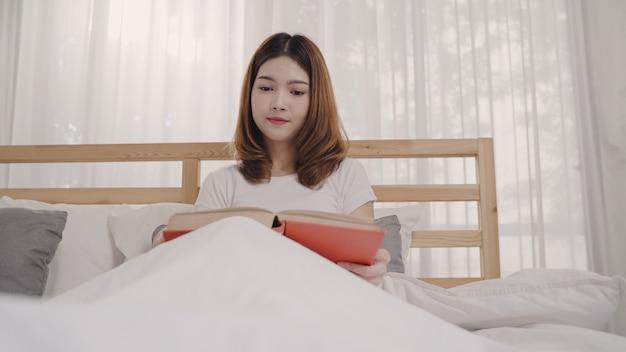 Schöne attraktive junge asiatin, die ein buch beim lügen auf dem bett liest
