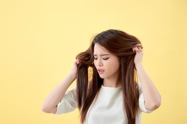 Schöne attraktive junge asiatische frau, die in beschädigten trockenen haaren schaut und sich so traurig und besorgt fühlt, isoliert auf weißem hintergrund, haarpflegekonzept