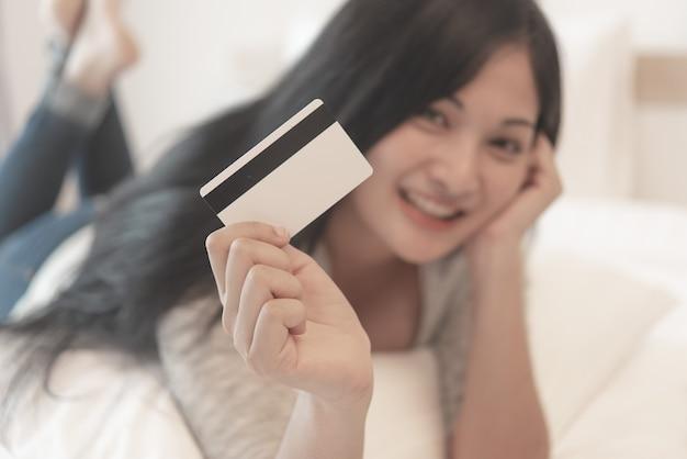 Schöne attraktive junge asiatische frau zeigen ihre kreditkarte für online kaufen