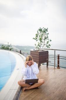 Schöne attraktive junge frau sitzt in der nähe eines großen pools und arbeitet an einem laptop. fernarbeit im urlaub.